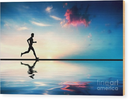 Silhouette Of Man Running At Sunset Wood Print