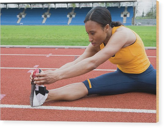 Athlete Stretching Wood Print by Gustoimages/science Photo Library