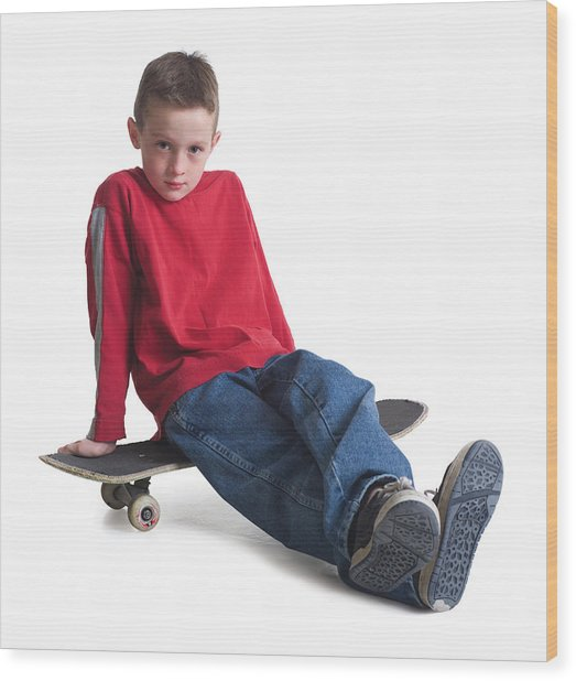 A Caucasian Boy In Jeans And A Red Sweater Sits On His Skateboard And Smiles Slightly Wood Print by Photodisc