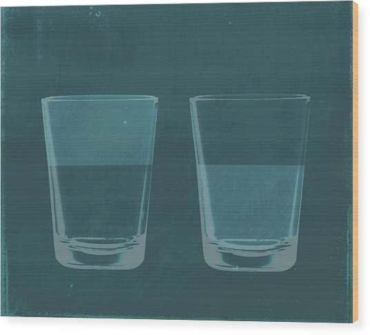 A Half Full Glass Of Water Next To A Wood Print