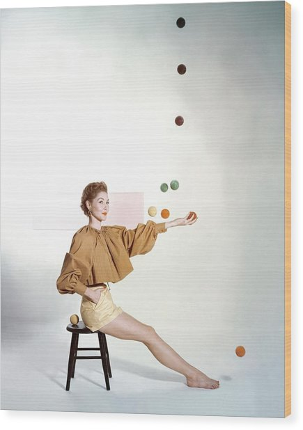 A Model Sitting On A Stool Juggling Wood Print