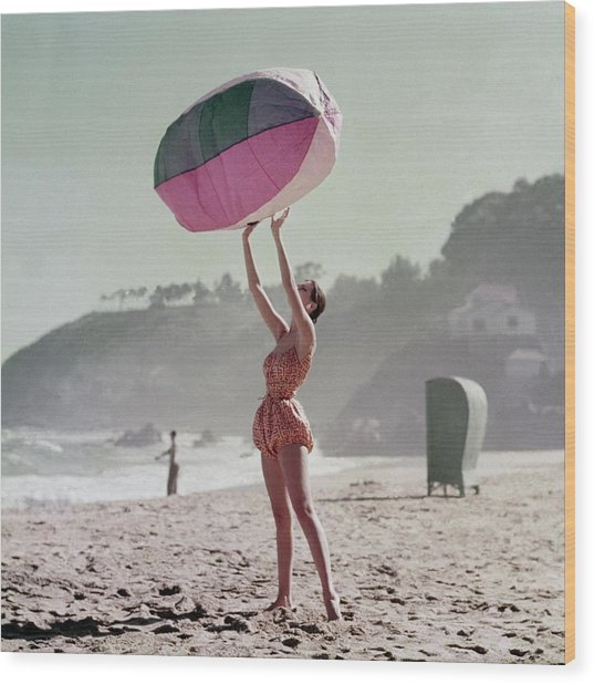 A Model Wearing A Bathing Suit Holding Up An Wood Print