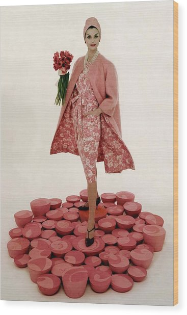 A Model Wearing A Matching Pink Outfit Holding Wood Print