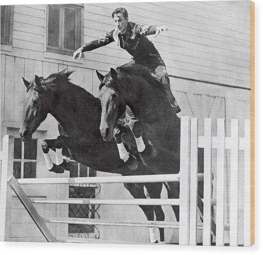 A Stunt Rider On Two Horses. Wood Print