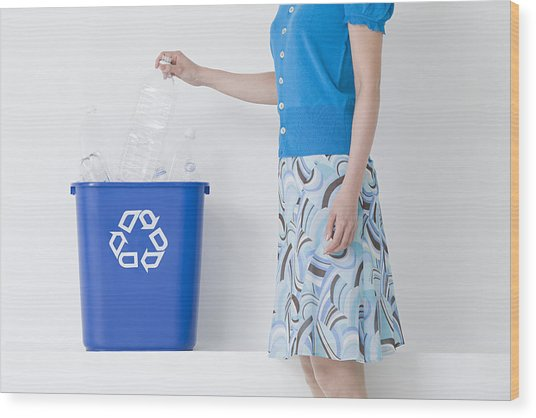 A Woman Putting A Bottle In A Recycling Bin Wood Print by Image Source