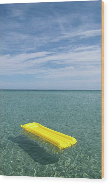 A Yellow Inflatable Raft Floating On Wood Print