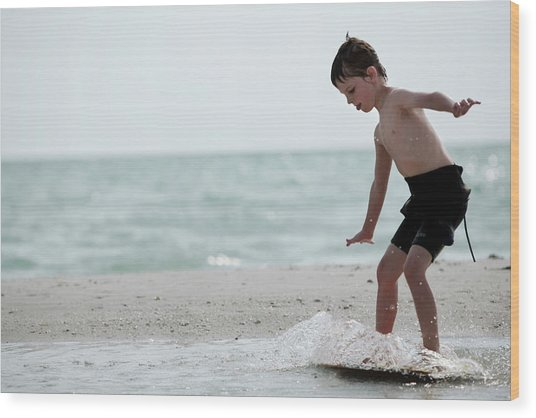 A Young Boy In A Wetsuit Surfs Wood Print