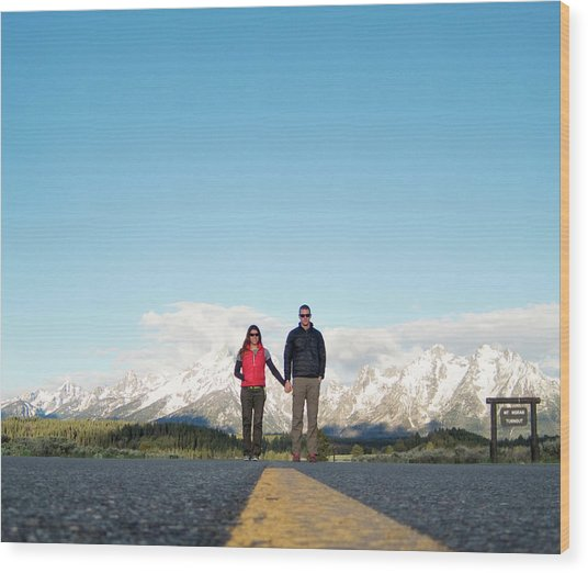 A Young Couple Holds Hands In Mountains Wood Print