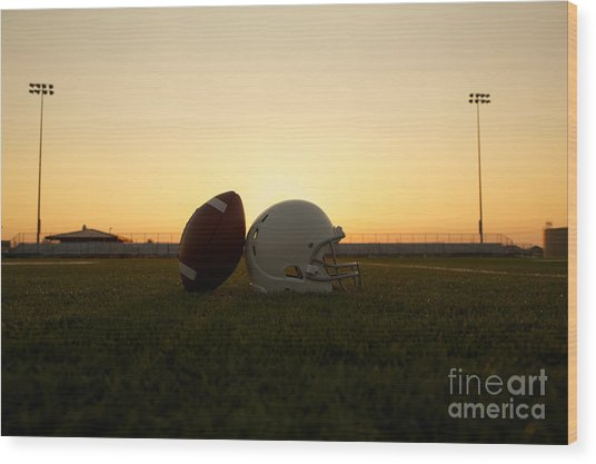American Football And Helmet On The Field At Sunset Wood Print