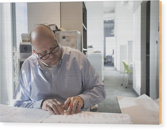Businessman Sketching Blueprints In Office Wood Print by Hill Street Studios