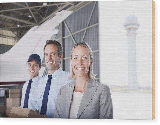 Businesswoman And Workers Standing In Hangar Wood Print by Martin Barraud