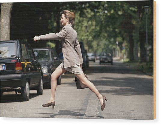 Businesswoman Running Across Road, Side View Wood Print by David De Lossy