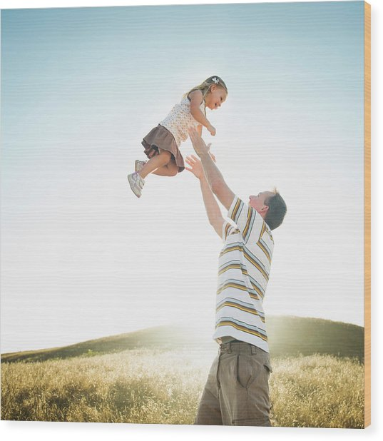 Caucasian Father Lifting Daughter Wood Print by Erik Isakson