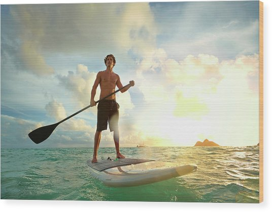 Caucasian Man On Paddle Board In Water Wood Print by Colin Anderson Productions Pty Ltd