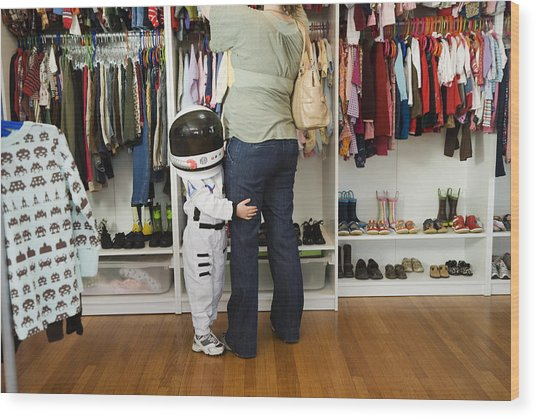 Child (4-5 Yeras) Wearing Space Costume Hugging Mother's Leg In Shop Wood Print by Inti St. Clair