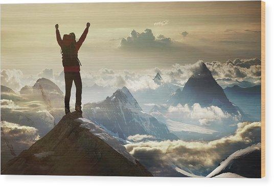 Climber Standing On A Mountain Summit Wood Print by Buena Vista Images