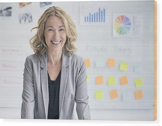 Confident Businesswoman Against Whiteboard Wood Print by Xavierarnau