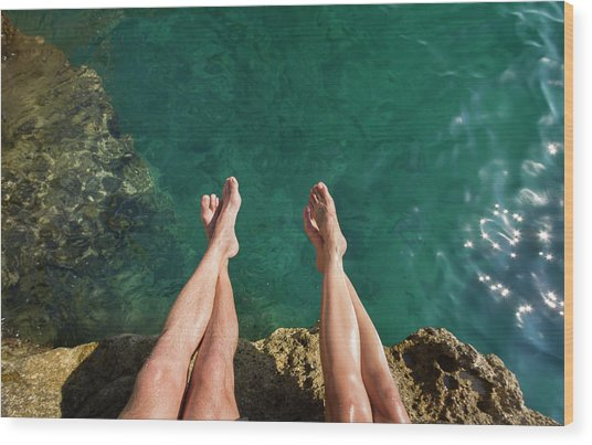 Couples Legs Above Turquoise Ocean Wood Print by Picturegarden