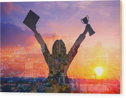 Digital Composite Image Of Woman Holding Award And Cityscape Against Sky During Sunset Wood Print by Jirapatch Iamkate / EyeEm