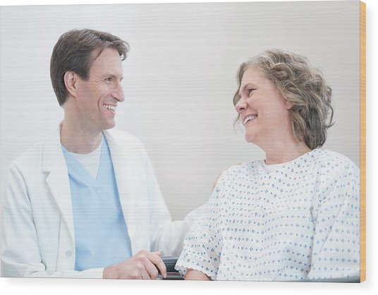 Doctor Smiling At Woman Patient Wood Print by Science Photo Library