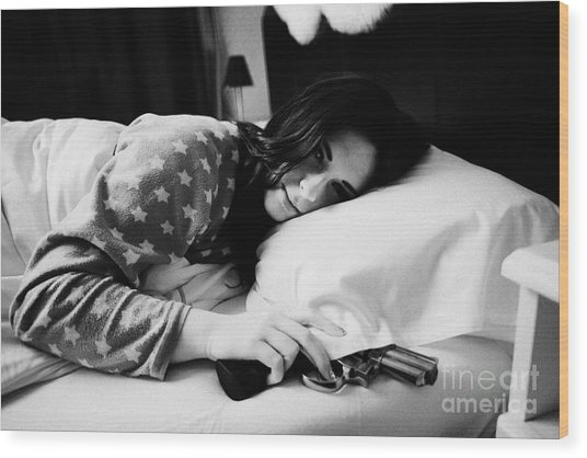 Early Twenties Woman Waking With Hand On Handgun Under Pillow At Night In Bed In A Bedroom Wood Print by Joe Fox