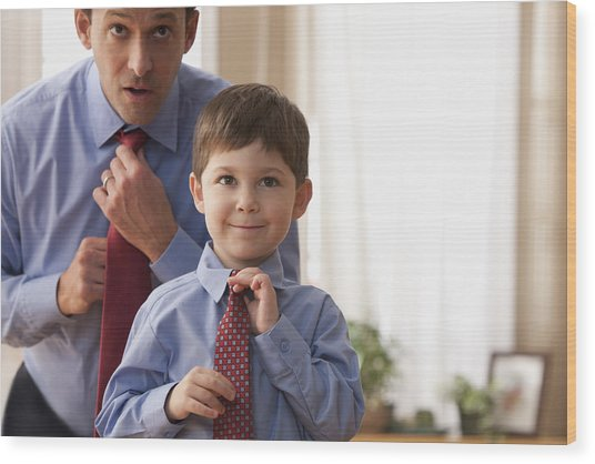 Father And Son Fixing Ties Together Wood Print by SelectStock