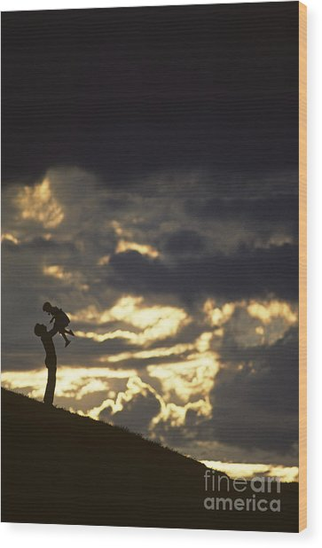 Father Holding Daughter Above His Head Along Hillside Silhouette Wood Print