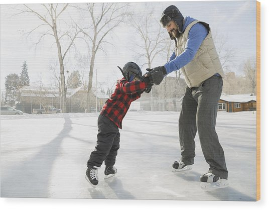 Father Teaching Son To Ice-skate On Outdoor Rink Wood Print by Hero Images