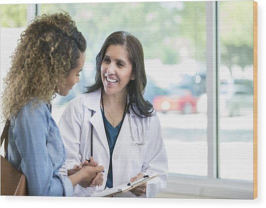 Female Doctor Discusses Something With Young Mixed Race Patient Wood Print by Asiseeit