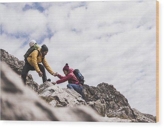 Germany, Bavaria, Oberstdorf, Man Helping Woman Climbing Up Rock Wood Print by Westend61