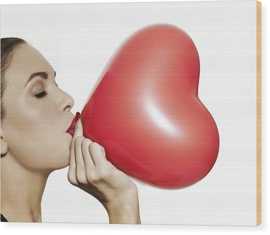 Girl Blowing Up A Red Heart Shaped Balloon Wood Print by Elizabeth Hachem