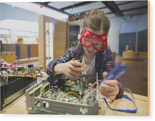 Girl Goggles Assembling Electronics Circuit At Science Center Wood Print by Hero Images