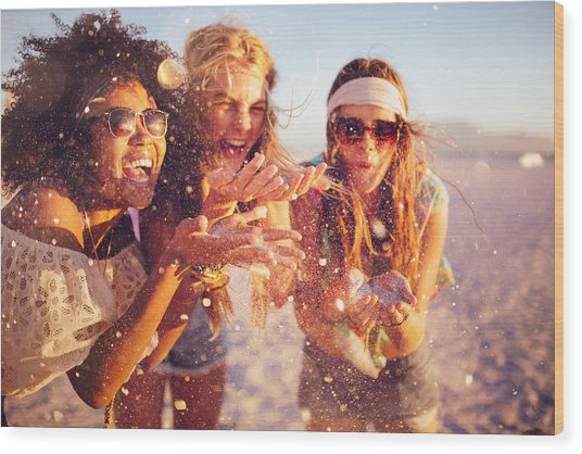 Girls Blowing Confetti From Their Hands On A Beach Wood Print by Wundervisuals