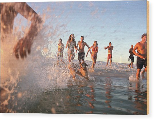 Group Of Young Adults Running Through Water At Ocean's Shore Wood Print by Sean Murphy