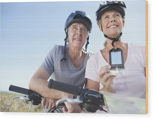Happy Mature Woman Mountain Biking With Man Using Gps Wood Print by OJO Images