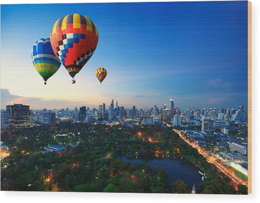 Hot Air Balloons Fly Over Cityscape At Sunset Background Wood Print by Busakorn Pongparnit