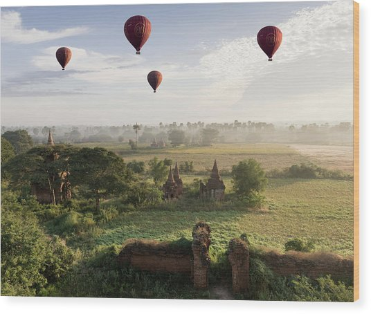 Hot Air Balloons Flying Over Ancient Wood Print by Martin Puddy