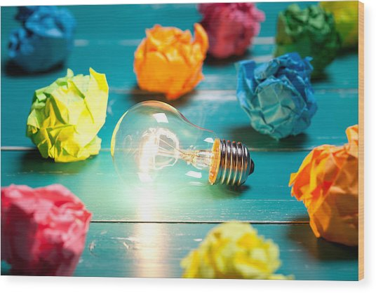 Incandescent Bulb And Colorful Notes On Turquoise Wooden Table Wood Print by Xxmmxx