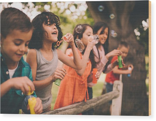 Little Boy Having Fun With Friends In Park Blowing Bubbles Wood Print by Wundervisuals