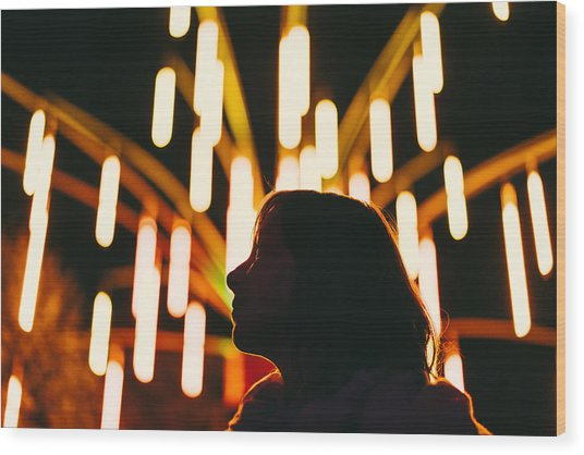 Low Angle View Of Silhouette Woman Against Illuminated Lights At Night Wood Print by Adriana Duduleanu / EyeEm