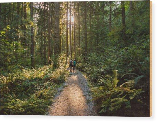 Man And Woman Hikers Admiring Sunbeams Streaming Through Trees Wood Print by PamelaJoeMcFarlane