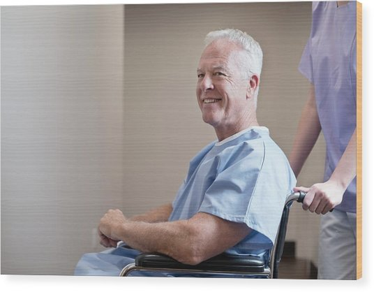 Man In Hospital Gown In Wheelchair Wood Print by Science Photo Library