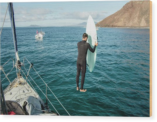 Man Jumping With His Surfboard In Water Wood Print