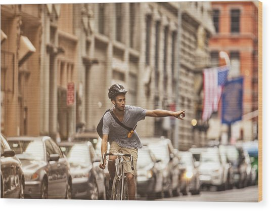 Man Riding Bicycle On City Street Wood Print by Sam Edwards