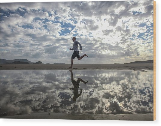 Man Running On Beach Wood Print by Paul Mansfield Photography