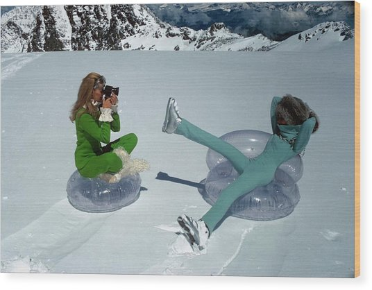 Models On Plastic Chairs With Snow In Switzerland Wood Print