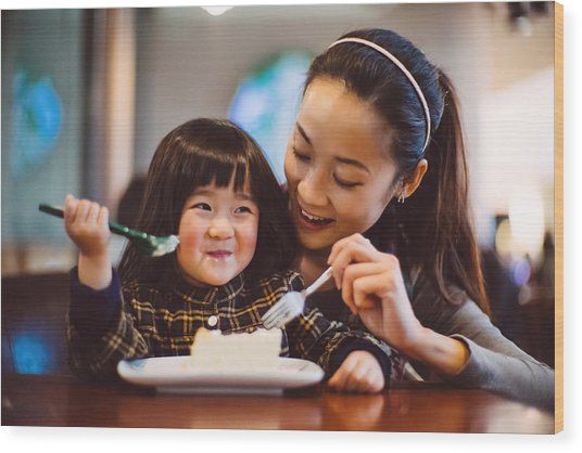 Mom & Toddler Girl Having Cake Joyfully In Cafe Wood Print by images by Tang Ming Tung
