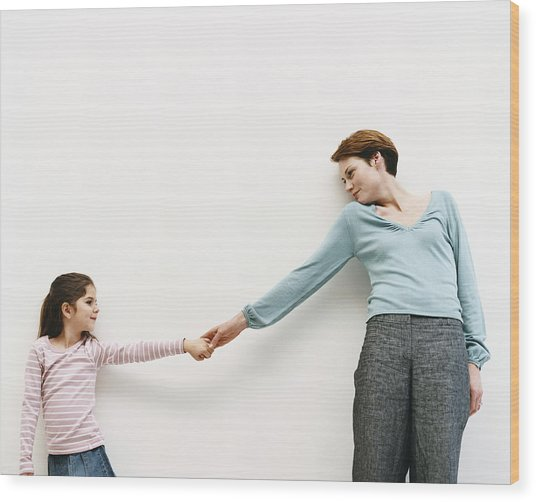 Mother And Her Daughter Stand By A Wall, Reaching Out And Holding Hands Wood Print by Dylan Ellis