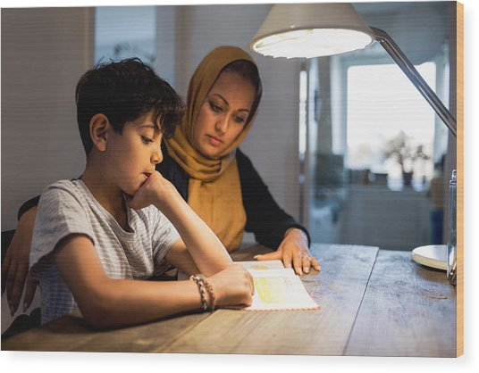 Mother And Son Reading Book Under Illuminated Desk Lamp At Home Wood Print by Maskot