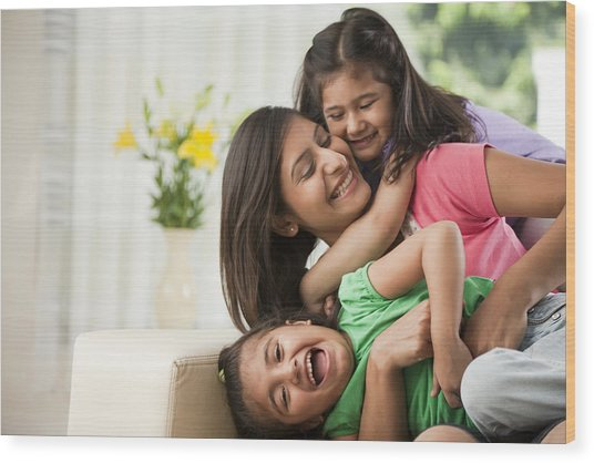 Mother With Daughters (6-7) Sitting On Sofa Wood Print by ImagesBazaar
